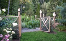 A Cedar Decorative Fence and Birdhouses Surround an Organic Vegetable Garden